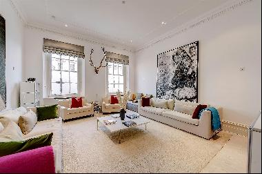 A rare ground and first-floor apartment in a grand white stucco-fronted building in the he